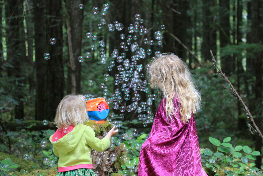 Two kids playing with bubbles