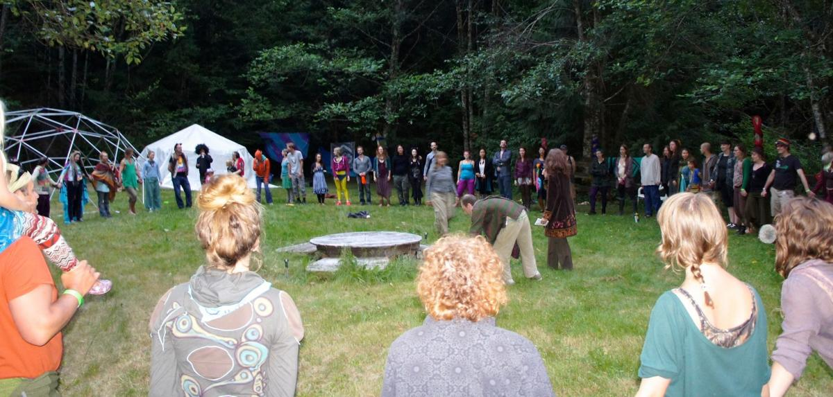 A group of people in a circle on a grassy field holding hands.  In the background is a geodesic dome, a tent and lots of trees.